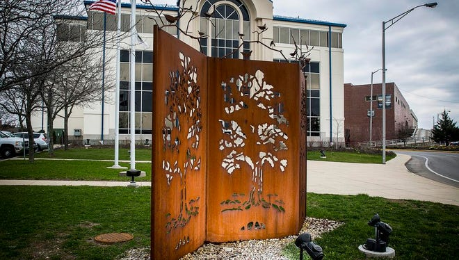 The sculpture Growing Through the Changes by artist Sally A. Myers outside City Hall in downtown Muncie Wednesday.