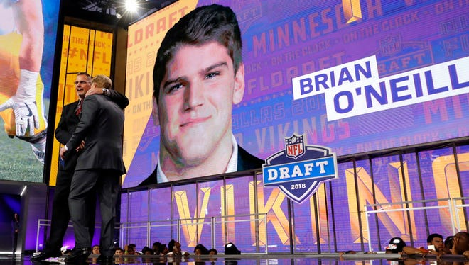 Former Minnesota Vikings player Keith Millard, left, embraces NFL Commissioner Roger Goodell after announcing Pittsburgh's Brian O'Neill as the Vikings' selection during the second round of the NFL football draft Friday, April 27, in Arlington, Texas.