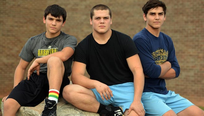 The Simonovich brothers, left to right, Dmitriy, 15, Mikhail, 18, and 16-year-old Peter stand outside the gym at  North Buncombe High School before the start of wrestling practice on Monday.
