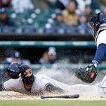 New York Yankees second baseman Gregorio Petit (31) slides safely at home plate as Detroit Tigers catcher Alex Avila (13) misses the tag during the first inning at Comerica Park.