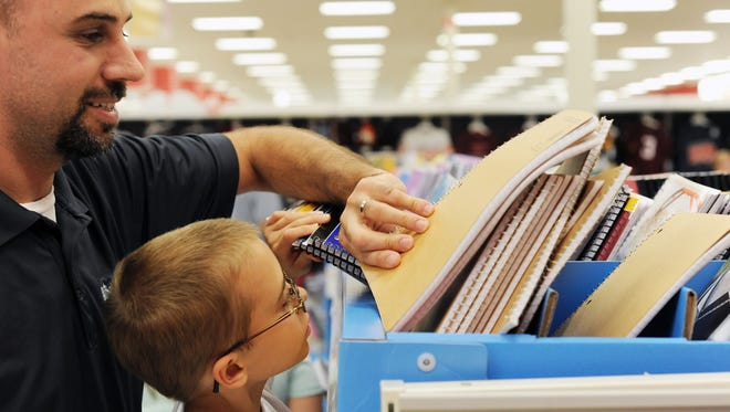 Jason Moore, left, helps his 8-year-old son Jackson pick out a spiral notebook during tax-free shopping at Target Aug. 2, 2013 in Lynchburg, Va.