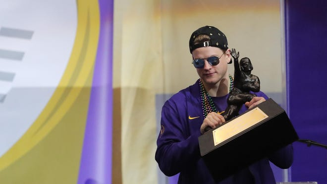 LSU quarterback Joe Burrow holds the Heisman Trophy.