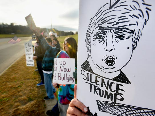 People hold signs during a silent protest of Republican