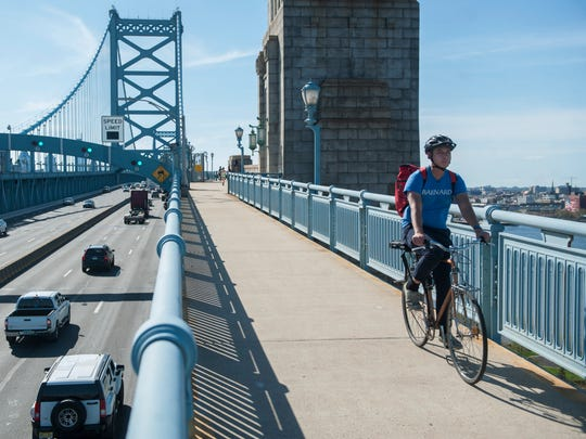 A bicyclist travels along the north walkway of the Benjamin Franklin Bridge near where a proposed billboard will stand, pictured to the right of the bridge. The proposed billboard at the base of the Benjamin Franklin Bridge has run into neighborhood opposition, even though the company seeking to build it is promising to donate all proceeds to city nonprofits.