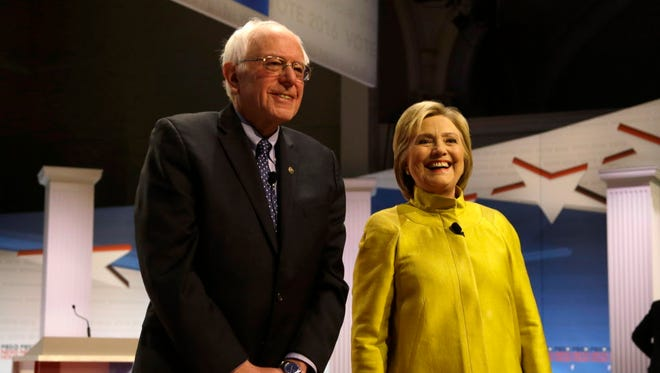 In this Feb. 11, 2016 file photo, Democratic presidential candidates Sen. Bernie Sanders, I-Vt, left, and Hillary Clinton smile as they take the stage before a Democratic presidential primary debate at the University of Wisconsin-Milwaukee.