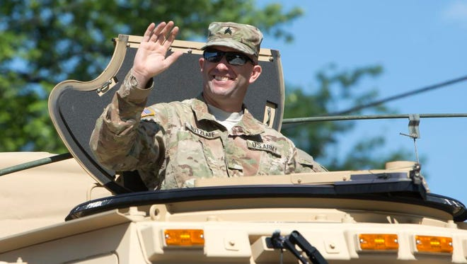 Military vehicles with military personnel drive trucks that Oshkosh Corp. has produced during the the company's 100-year parade celebration July 15, 2017.
