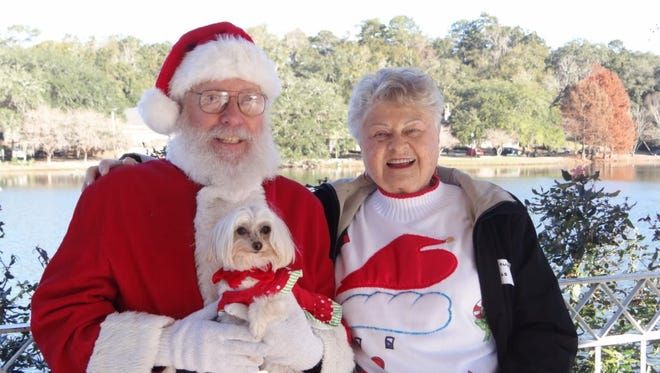 Carol Burlison, right, and her dog Peaches spend some quality time with Santa at the Santa Paws Walk. This year's canine party is Saturday at Lake Ella.