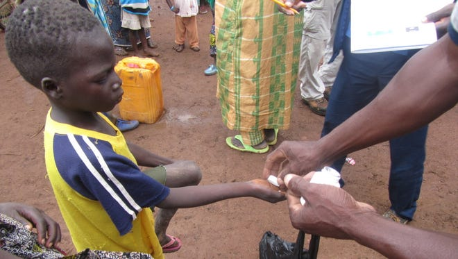 A young villager in Burkina Faso receives an ivermectin pill.