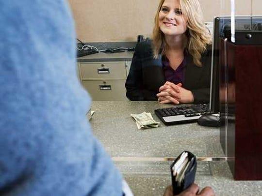 A bank teller smiling at a customer.