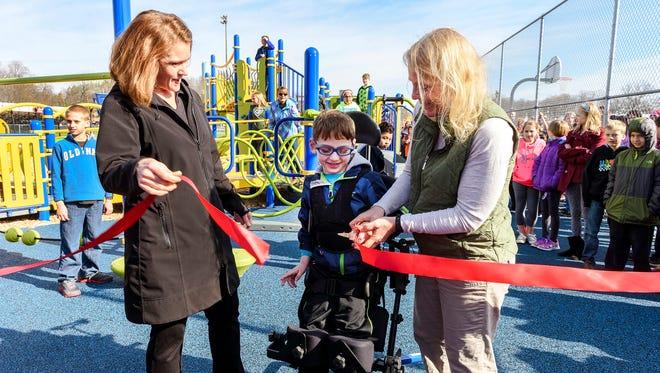 Ethan DeZwarte, junior kindergarten student, cuts the ribbon to the new playground at Elkhart Lake-Glenbeulah Elementary School.