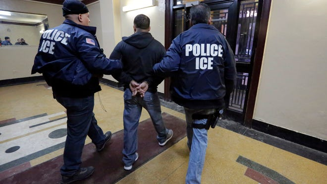 Immigration and Customs Enforcement officers escort an arrestee from an apartment building March 3, 2015 in the Bronx borough of New York during a series of early-morning raids.