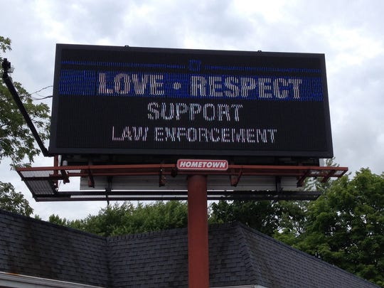 """A sign reading """"Love, Respect, Support Law Enforcement"""" appeared on this electronic billboard along Wheeling Avenue on Monday, two days after an earlier one reading """"Hate cops? The next time you need help call a crackhead"""" prompted controversy."""
