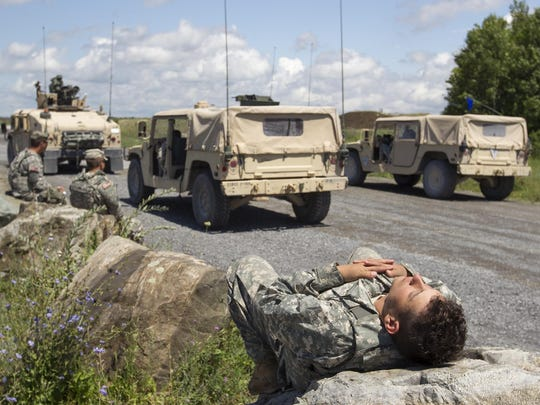 Spc. Zack Clark of Hornell catches a nap near some of the company's Humvees as the soldiers await clearance to resume using the range for live fire training at Fort Drum.