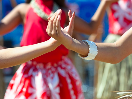 Chamorro dancers cross hands during a performance.