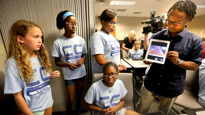 MTSU Code Camp students back row Chloe Randolph, 12; Condoleezza Rankins, 12; and Addesn Frink, 11; and, bottom row, Nora Peebles-Ross, 11, ask questions to Liam Nilsen, online from MIT, one of the inventors of the Makey Makey a invention kit, as camp director David Lockett holds the iPad.