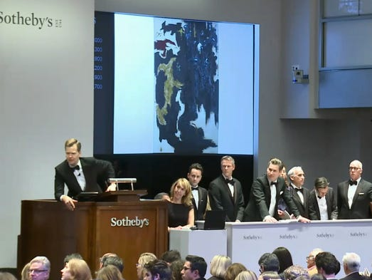 Auctioneer Oliver Barker calls for bids on a painting