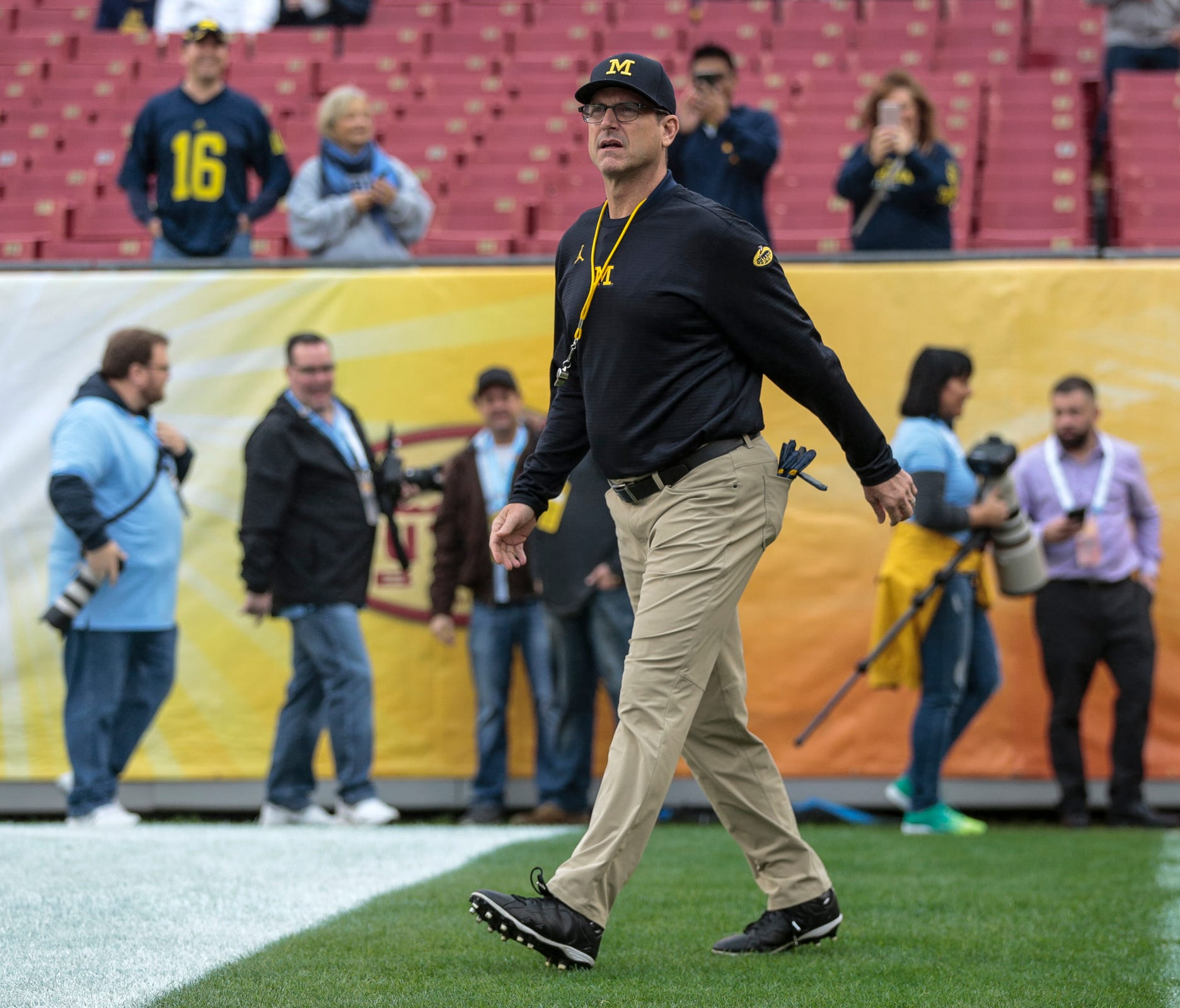 Michigan Wolverines head coach Jim Harbaugh enters the field for the Outback Bowl at Raymond James Stadium in Tampa, Fla., Monday, Jan. 1, 2018.