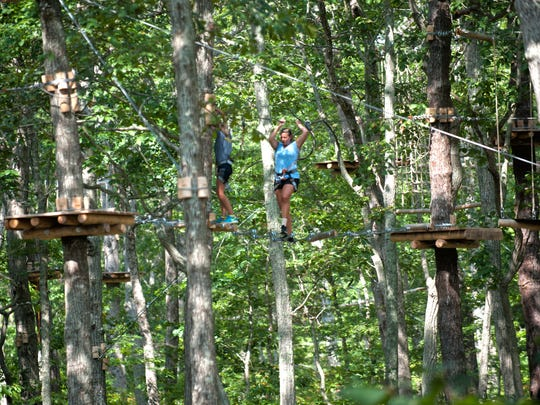 Participants cross over obstacles on their way to the the new zip-line course Tree to Tree Adventure Park at Cape May Zoo,