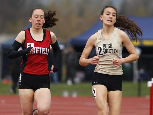 Katie Lembo of Penfield, left, and Alex Cooper of Rush-Henrietta compete in the 1,500-meter run at the His and Her track and field invitational at Penfield High School on Saturday, April 26, 2014. Cooper won the event.