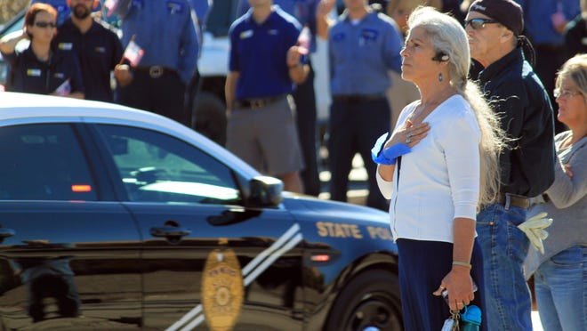 Kathleen Oweegon, of Albuquerque, puts her hand over her heart as the funeral procession of slain Albuquerque Police Officer Daniel Webster passes in Albuquerque on Tuesday.