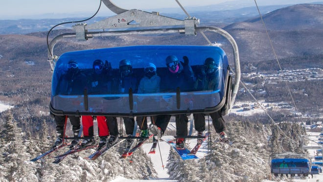 """Skiers wave from a """"bubble chair"""" on Mount Snow Resort's Bluebird Express Lift."""