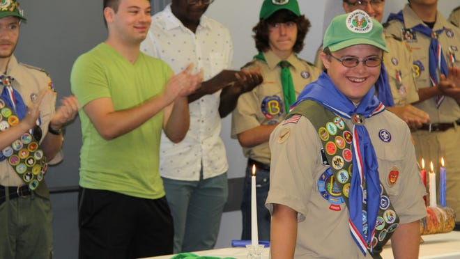 Zachary Adams, 19, of Kendall received his Eagle Scout award on July 10 at the Brockport Elks Lodge in Sweden. Behind him are some of the two dozen Eagle Scouts of all ages who attended his ceremony.