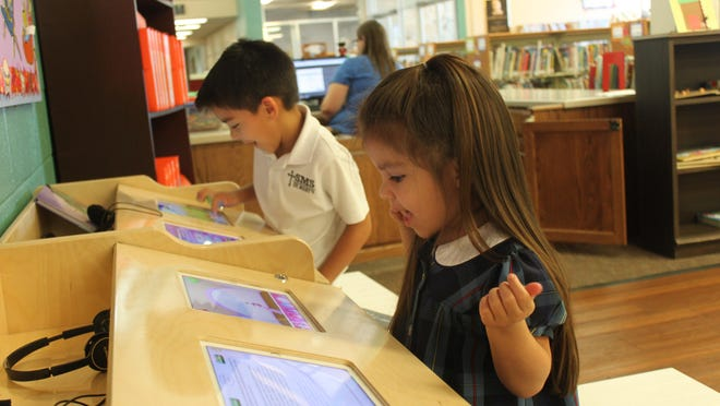 Sofia and Eros Aguirre use the Jackson-Madison County Library's new iPads in the children's section of the downtown location.