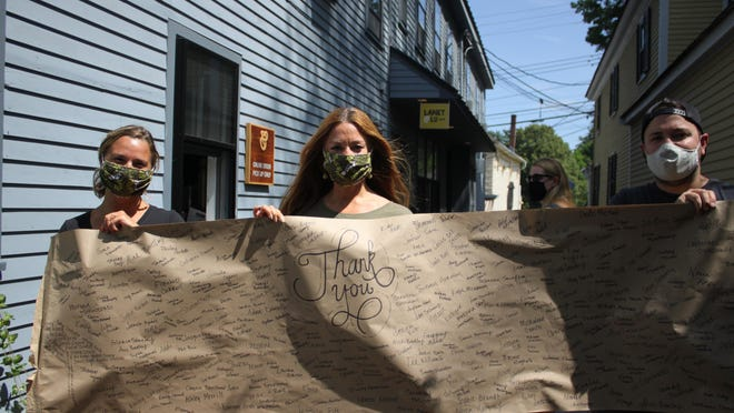 Laney & Lu employee Stef Heitz, owner Jennifer Desrosiers and Kaleb Travers hold up their Gratitude Banner, thanking customers for donating meals to frontline workers and those in need during the pandemic
