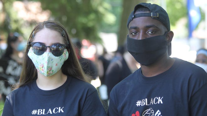 Two young adults participate in last month's Black Lives Matter peaceful protest in Kewanee wearing face coverings.