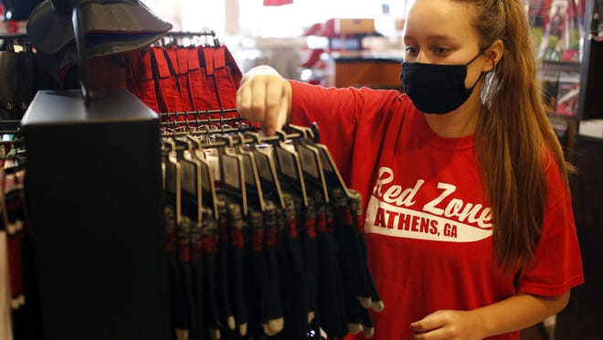 Alyssa May sets up Georgia football merchandise at the Red Zone in downtown Athens on Thursday.