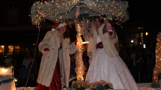 Angels dressed in white adorn a lighted float.