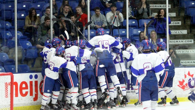 Novi Detroit Catholic Central players pile on each other after winning Friday's Division 1 semifinal over University of Detroit Jesuit at Compuware Arena.