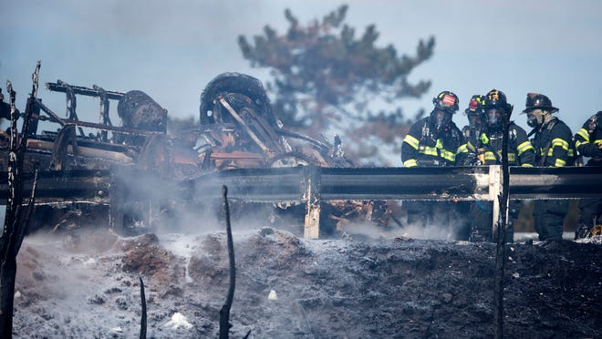 Firefighters work the scene of a tanker truck fire Monday, Feb. 23, 2015, in Pennsauken, N.J. The fire broke out shortly after 11 a.m. Monday, when the truck carrying nearly 9,000 gallons of fuel overturned on the Route 90 on-ramp to Route 130 in Pennsauken. (AP Photo/Matt Rourke)