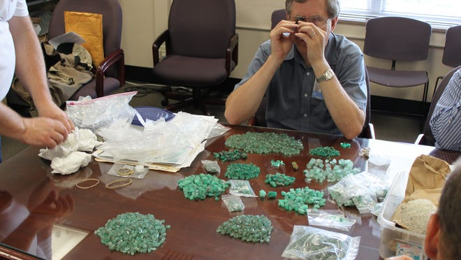 Dr. Jeffrey Post, gem curator at the Smithsonian Institute, inspects emeralds Jay Miscovich said he found off the coast of Key West, Florida. They were later determined to be fake. A Key West salvage company is trying to have a Delaware law firm sanctioned for bad faith litigation.