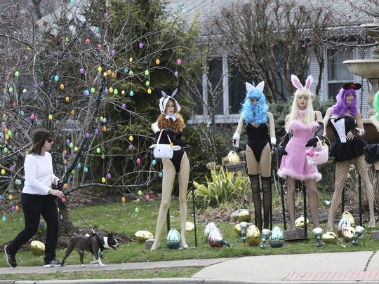A woman walks her dog past an Easter display in Clifton,
