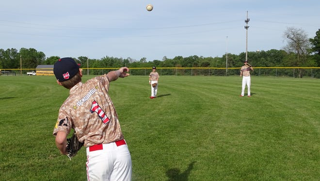 Tanner Compton warms up with Grant Burkholder before practice Monday. The 13U Athletics are one of five Athletics Baseball Association teams wearing commemorative Fallen Heroes jerseys this weekend.