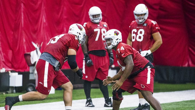 Arizona Cardinals offensive linemen Will Holden, (69), left, and D.J. Humphries, (74) prepare to collide during practice as Vinston Painter, (78) upper left, and Jared Veldheer, (68) upper right,  watch in the bubble at the training facility in Tempe, Friday, September 29, 2017.