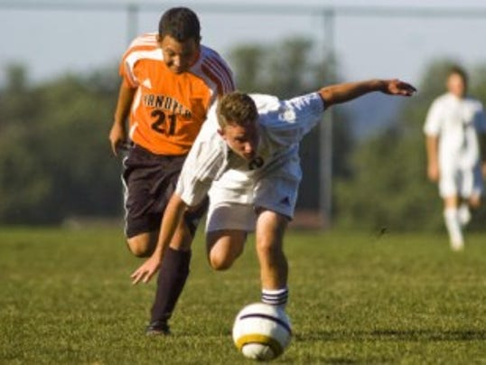 South Western's Eric Weldon struggles to regain balance while chasing down a loose ball against Hanover's Alex Guzman during Wednesday's boys' soccer match at South Western High School. (The Evening Sun -- Shane Dunlap)