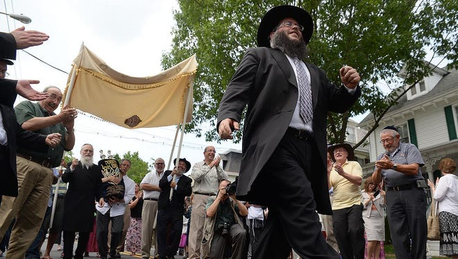 Rabbi Yitzchok Kahan of Chabad in Medford (right) precedes the newly completed Torah scroll (left) in the Torah parade down Main Street in Medford on Sunday.