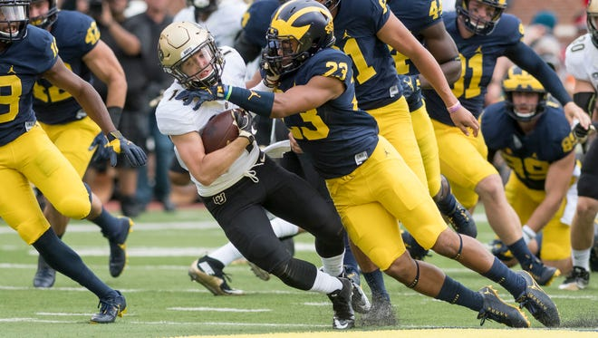 Michigan's Tyree Kinnel tackles Colorado Buffaloes wide receiver Jay MacIntyre in the first half of the Wolverines' win Saturday.