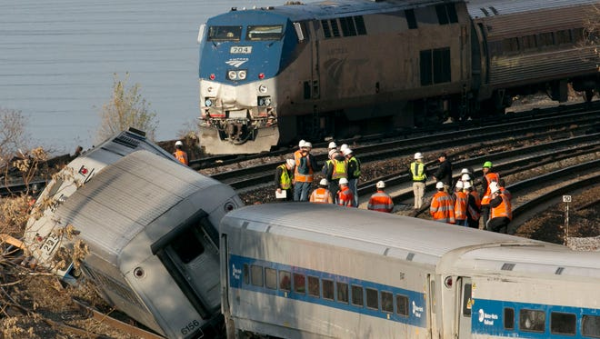 In a Dec. 1, 2013, file photo, an Amtrak train, top, traveling on an unaffected track, passes a derailed Metro North commuter train, in the Bronx borough of New York. President Donald Trump is putting the brakes on attempts to address dangerous transportation safety problems from speeding tractor-trailers to sleepy railroad engineers as part of his quest to roll back regulations across the government.