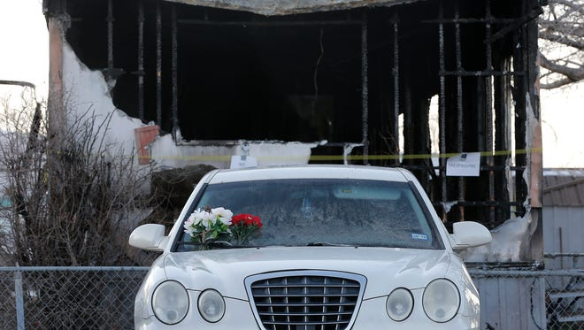 Flowers and a crucifix were placed in the windshield of 32-year-old Alejandro Saenz in front of his burned trailer home in northeast El Paso. Saenz died in the fire.