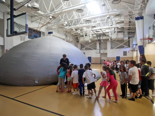 Students line up to enter a planetarium at Paideia School 15. The planetarium was funded by the PTA.
