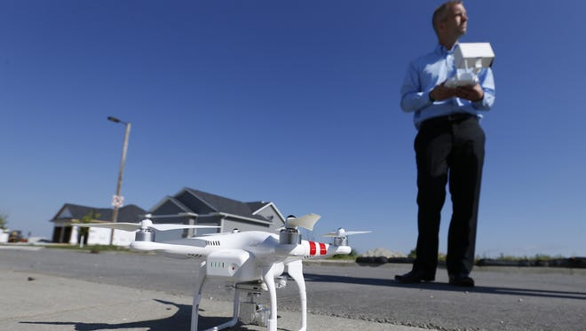 Justin Dodge, development coordinator with Hunziker Land Development, explains how his company plans to use their drone Monday, June, 1, 2015, in front of one of their properties in Ames.