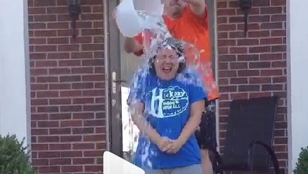 Jolene Benedict of Burlington is dumped with a bucket full of ice by her husband, Ron, in the ALS Ice Bucket Challenge.