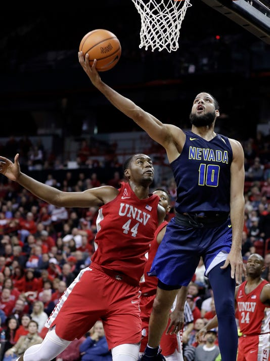 Nevada's Caleb Martin shoots as UNLV's Brandon McCoy defends during the first half of an NCAA college basketball game Wednesday, Feb. 28, 2018, in Las Vegas. (AP Photo/Isaac Brekken)