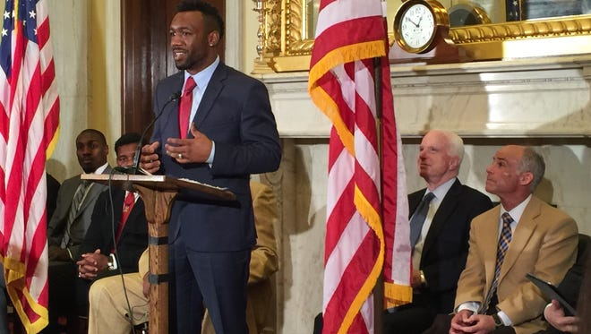 Boxer Austin Trout speaks at a Capitol Hill press conference about the Cleveland Clinic's ongoing study of brain injury among professional fighters. Arizona Senator John McCain and the study's chief investigator, Dr. Charles Bernick, look on.