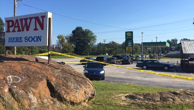 Investigators at the scene of TD's Express Mart, where a suspect hit a deputy and fled the scene.