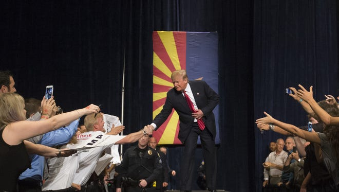 Republican presidential candidate Donald Trump greets the crowd during a rally at the Phoenix Convention Center on Saturday, July 11, 2015.