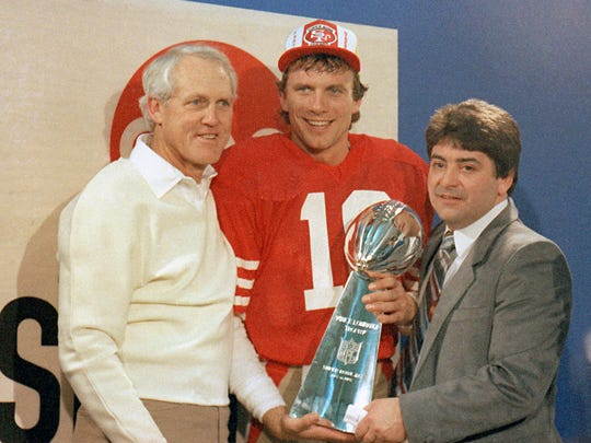 In this 1985 photo, Joe Montana holds the Lombardi Trophy with coach Bill Walsh (left) and 49ers owner Ed DeBartolo Jr.